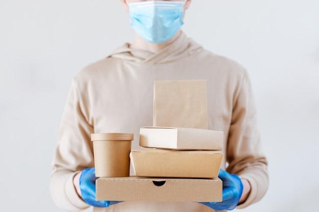 전염병 코로나바이러스. 커피, 패스트푸드 패키지. 비접촉식 음식 배달. 장갑과 마스크를 쓴 택배는 에코 포장을 들고 있습니다. 집에 있어, 안전해