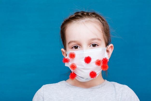 流行性covid-19。コロナウイルスに囲まれた医療用マスクを着た少女