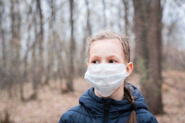 流行性covid-19。医療マスクをかぶった少女が人けのない森を一人で歩く。隔離と検疫。