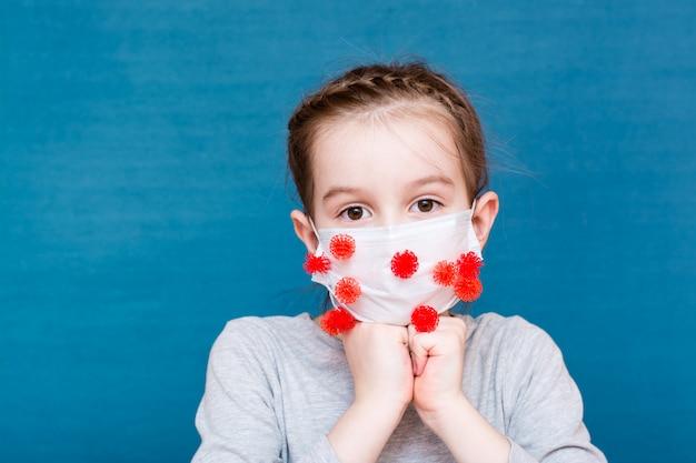 流行性covid-19。コロナウイルスに覆われた医療マスクのおびえた女の子
