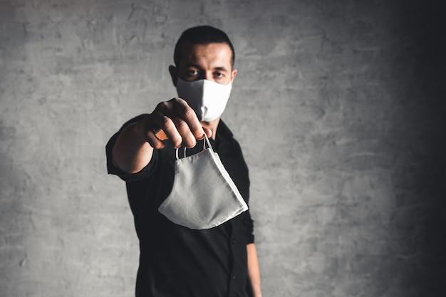 Эпидемиолог, предлагающий защитную респираторную маску в концепции коронавируса, выборочный фокус
