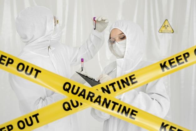 防護服を着た疫学者の女性がプランシェットのある制限区域にいます。科学者の医師のバイオハザード防護服を手にしたサンプルチューブ内の感染した血液サンプル