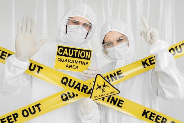 전염병 학자 보호 복을 입은 남자와 여자는 위험 표시가있는 제한 구역에 있습니다. 노란색 선 격리 보관. 격리 구역에서는 출입이 금지됩니다. 코로나 바이러스 (코로나 19.