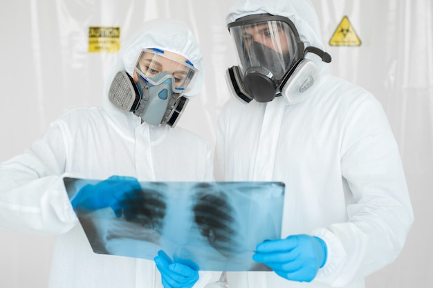 Epidemiologists in respirators examine the patient's pneumonia on a radiograph covid-19. concept of coronavirus