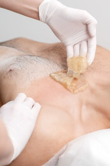 미용실에서 여성 미용사의 손에 의해 액체 왁스 페이스트로 젊은 남성의 제모 가슴