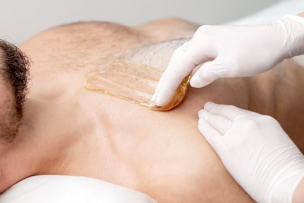 Epilation chest of young male with liquid wax paste by hands of female cosmetologist in beauty salon
