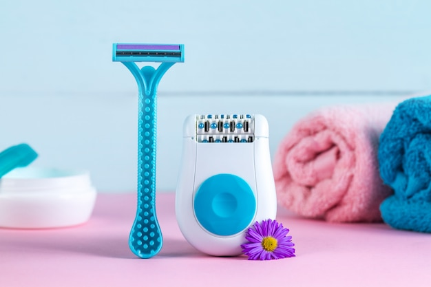 Epilator, cream, women's shaving razor, towels and flowers. depilatory. removal of unwanted hair. epilation concept