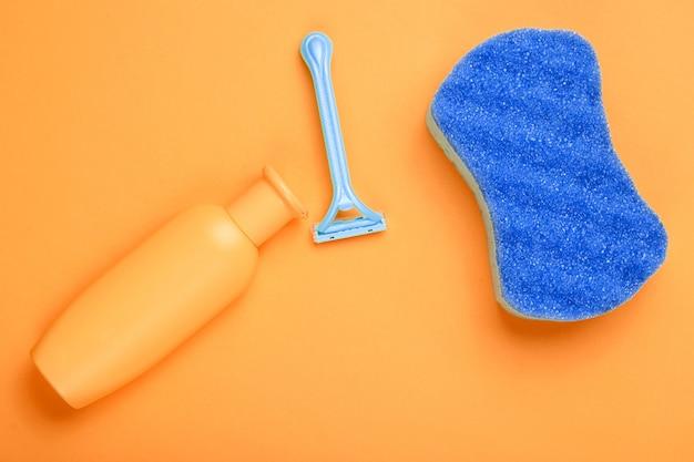 Эпилятор бритвы, губка, бутылка шампуня на оранжевом фоне