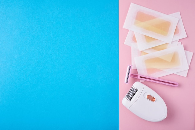 Epilator, razor and wax strips on blue and pink