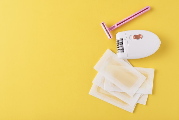 Epilator, razor and wax strips on yellow surface