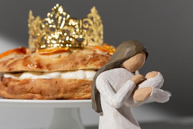 Statuetta femminile del giorno dell'epifania con neonato e dessert