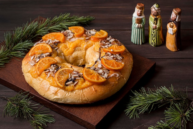 Epiphany day food with sliced oranges and miniature holy characters