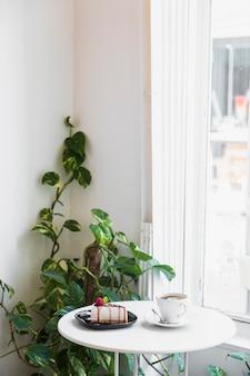 ゴールデンポトスまたはepipremnum aureum植物の近くのテーブルの上のチーズケーキとコーヒーカップ