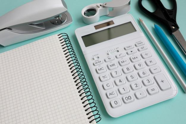 白い電卓と文房具は現代青いテーブルeptyにあります。