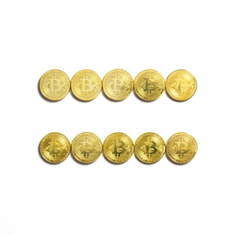 The equal symbol  laid out of bitcoin coins and isolated on white background