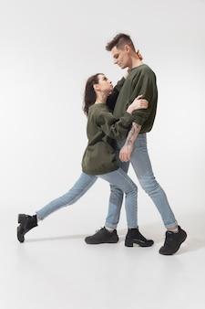 平等。白いスタジオの壁に分離されたトレンディなファッショナブルなカップル。