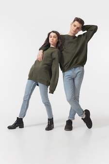 Equality. trendy fashionable couple isolated on white  wall. caucasian woman and man posing in basic minimal unisex clothes. concept of relations, fashion, beauty, love. inclusive.
