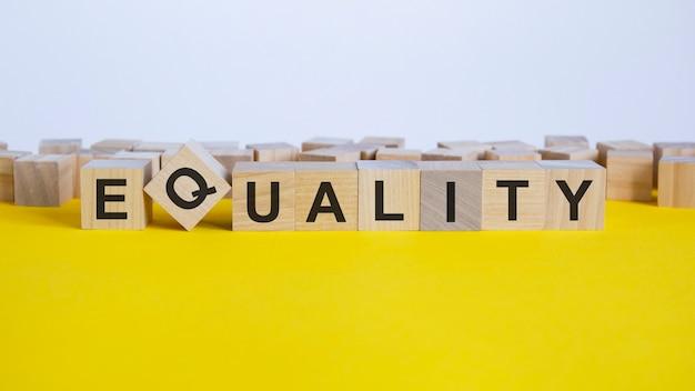Слово равенство состоит из деревянных строительных блоков, лежащих на желтом столе, концепция