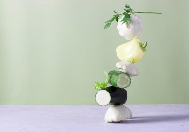 明るい背景に新鮮な野菜を浮かぶ平衡。コピースペース