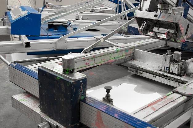 縫製工場のクローズアップで布を塗装するための機器と機械