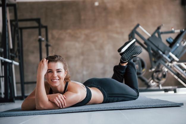 뒤에 장비. 그녀의 주말 시간에 체육관에서 화려한 금발 여자의 사진