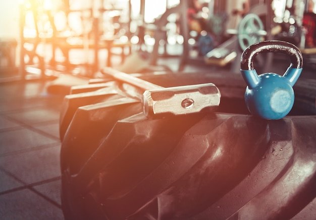 ファンクショナルトレーニング用の機器。ジムの大きなゴム製の車輪、ハンマー、ケトルベルのクローズアップ。クロストレーニング