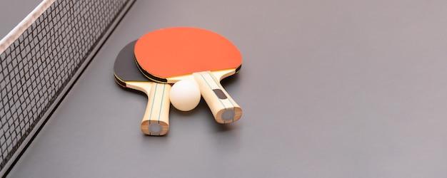 Оборудование для настольного тенниса - ракетки, мяч, стол, сетка. баннер. копировать пространство