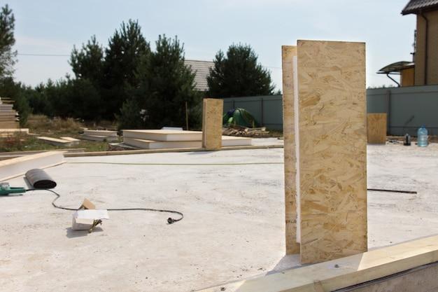 Оборудование, лежащее на строительной площадке с разбросанными инструментами и деревянными изоляционными панелями на свежеуложенном бетонном полу нового дома.
