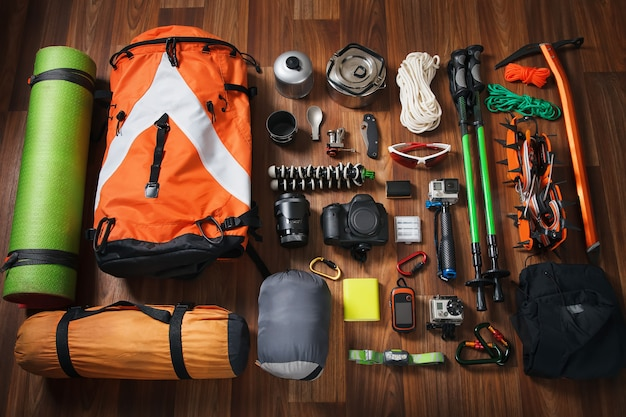 Equipment necessary for mountaineering and hiking on wooden background