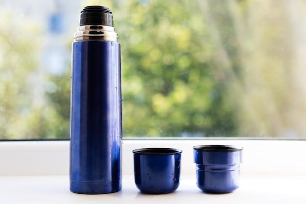 ふた付きの青い魔法瓶の機器。