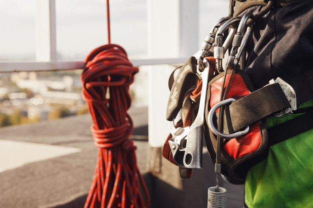 산업 고층 작업 동안 건물 지붕에 산업 등산 노동자의 장비. 작업을 시작하기 전에 등반 장비. 밧줄 노동자 접근. 도시 작품의 개념입니다. 복사 공간