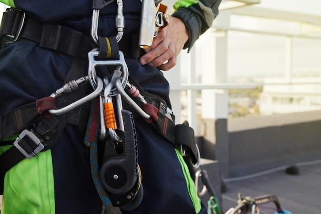 工業用高層工事中の建物の屋根にある工業用登山作業員の設備。仕事を始める前に機器を登る。ロープ労働者のアクセス。都市作品のコンセプト。コピースペース