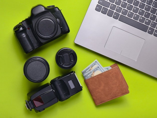 Equipment  photographer, laptop, purse with dollars on a green background. freelance concept, photographer's work, objects, top view, flat lay