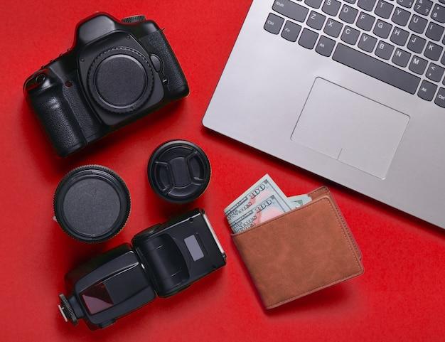 Снаряжение фотографа, ноутбук, кошелек с долларами на redbackground