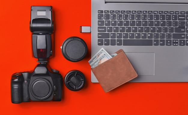Equipment  photographer, laptop, purse with dollars on red background