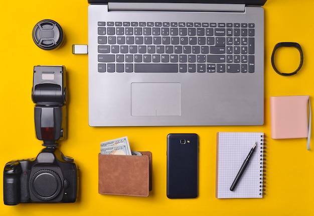 Оборудование фотограф, ноутбук, кошелек с долларами, смартфон, умные часы, банк питания, на желтом фоне. внештатная концепция, гаджеты для работы, объекты, вид сверху, плоская планировка