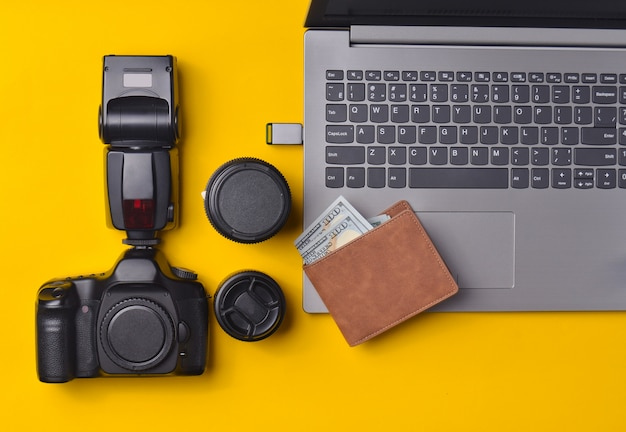 Equipment  photographer, laptop, purse with dollars on a yellow background. freelance concept, photographer's work, objects, top view, flat lay