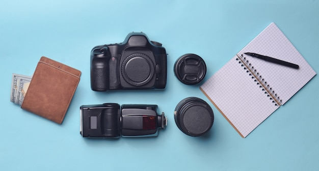 Equipment  photographer, purse with dollars, notebook on a blue pastel background. freelance concept, photographer's work, objects, top view, flat lay