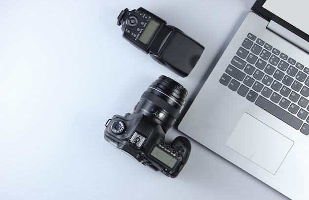 灰色のテーブル上の機器のプロのカメラマン。ラップトップ、カメラ、フラッシュ。