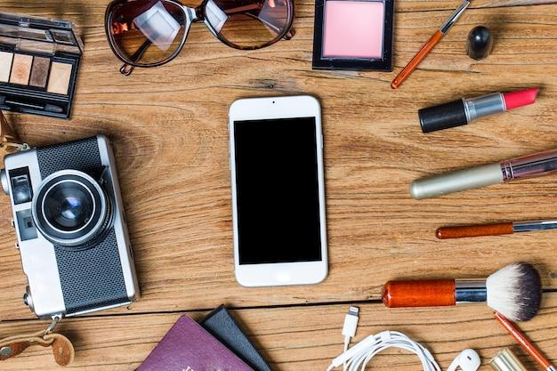 Оборудование тур по подростковой девушке, косметика, аксессуары, макияж, смартфон, сумка, шляпа готовы к путешествию.