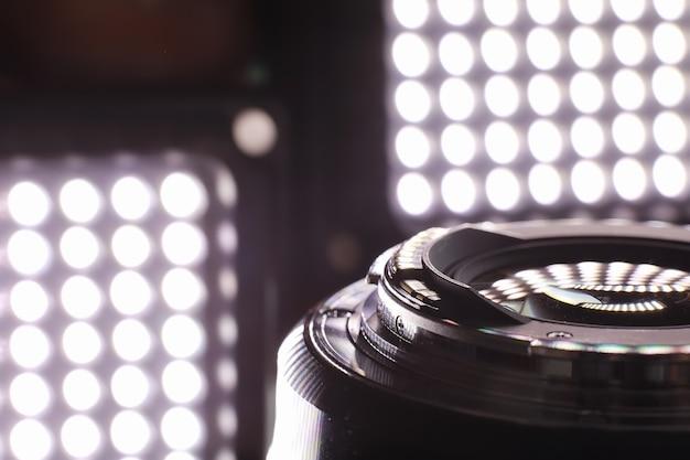 장비 비디오그래퍼이자 사진작가. 밝은 램프의 배경에 대해 테이블에 렌즈. 카메라 유리에 반사된 눈부심과 보케.