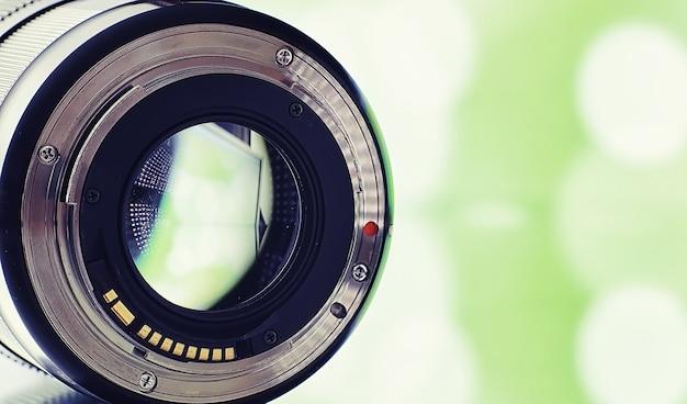 機器の映像作家および写真家。明るいランプを背景にしたテーブルのレンズ。カメラガラスの反射のまぶしさとボケ味。