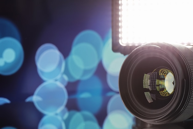 Equipment videographer and photographer. lenses on the table against the background of bright lamps. glare and bokeh in the reflection of the camera glass.
