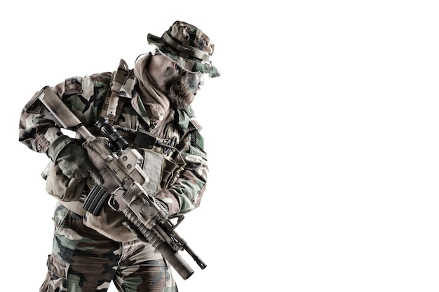 소총 특공대원, 미 육군 특수부대 군인, 위장복을 입은 해병대원, 부니 모자를 쓰고 뒤를 돌아보고 흰색으로 격리된 모퉁이 스튜디오 촬영 주위를 들여다보고 있습니다.