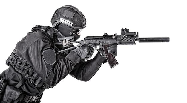Оборудованный солдат армии, член элиты спецназа, боец-коммандос, стрелок полицейского спецназа, защищенный бронежилетом и шлемом, прицеливается из штурмовой винтовки, изолированные на белом фоне
