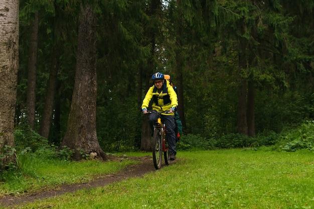 Оборудованный велосипедист-турист едет по тропе в еловом лесу.