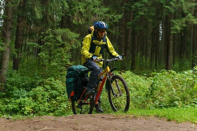 Снаряженный велосипедист-мужчина пересекает овраг в еловом лесу с ускорением