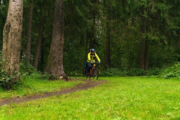 Снабженный велосипедист-мужчина едет по тропе в еловом лесу.