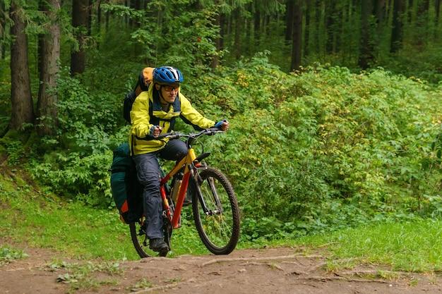 Оборудованный велосипедист-мужчина пересекает овраг в еловом лесу с ускорением