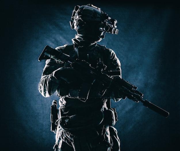 현대 탄약, 소음기가 달린 무장 돌격 소총, 전투 헬멧 코만도 군인 낮은 키에 4개의 렌즈 야간 투시경으로 어둠 속에 서 있는, 검은 배경에 스튜디오 초상화